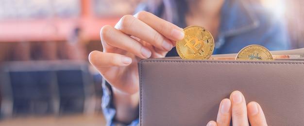 La main d'une femme tire une pièce de bitcoin d'un portefeuille.