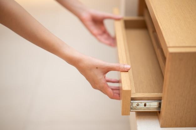 Main de femme tirez l'armoire en bois à tiroir ouvert.