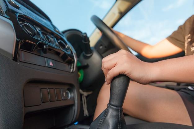 Main de femme touchant la boîte de vitesses
