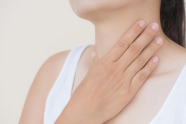 Main de femme touchant son cou mal. concept de soins de santé.
