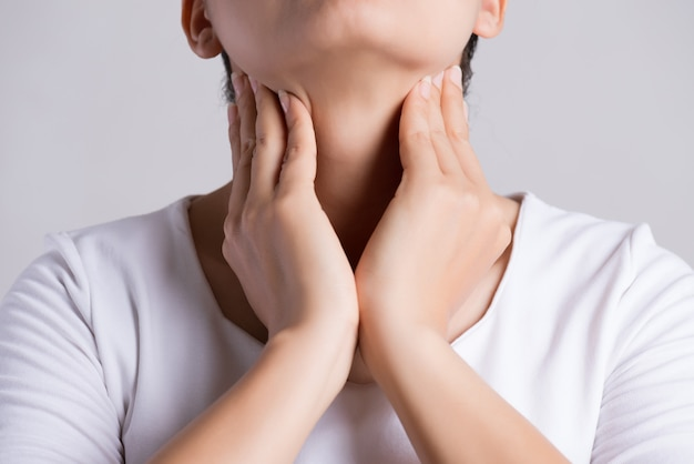 Main de femme touchant son cou malade.
