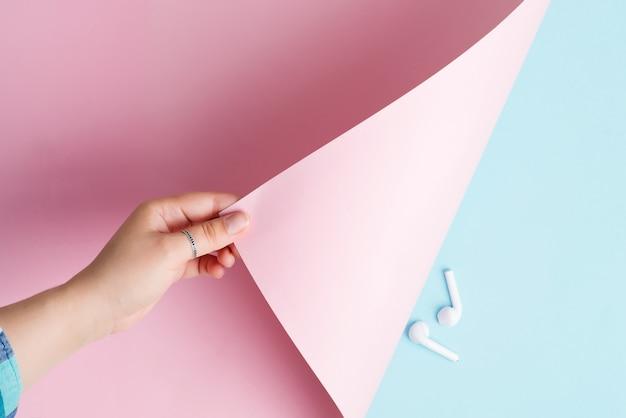 Main de femme tourne une feuille de papier de couleur rose pastel sur un fond bleu clair avec une paire d'écouteurs.