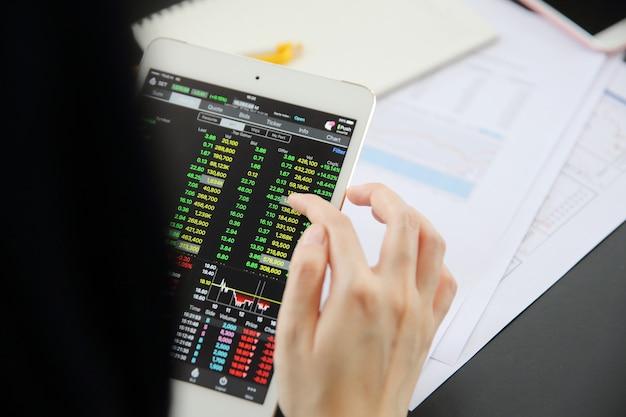 Main de femme trading en ligne sur tablette avec papier d'affaires et café