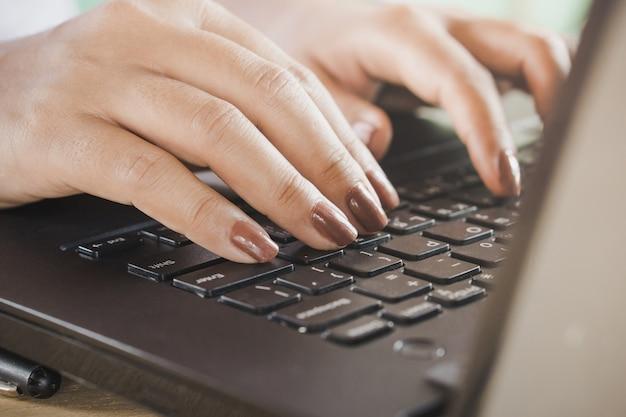 Main de femme travaillant sur ordinateur portable de bureau à domicile, taper sur le clavier