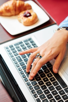 Main de femme travaillant sur ordinateur portable