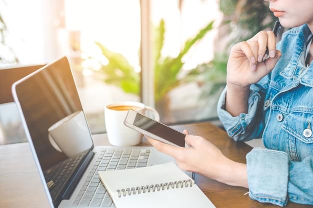 La main d'une femme travaille sur un ordinateur portable et un téléphone portable au bureau.