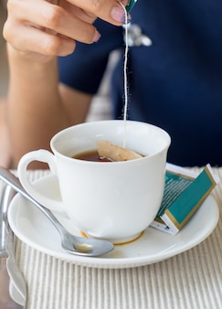 Main femme trempée dans une tasse à thé