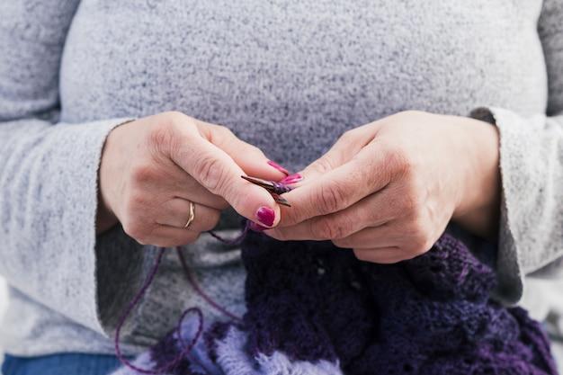 Main de femme tricotant le foulard en laine avec des aiguilles tricotées