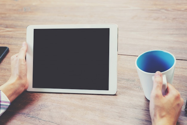 Main femme utilisant un ordinateur tablette sur une table en bois avec vintage tonifié.