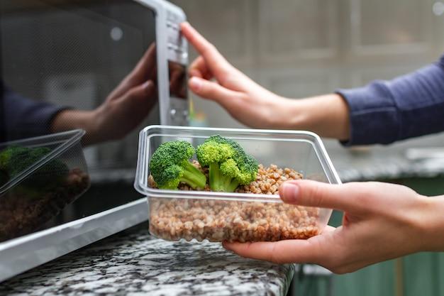 La main de femme va chauffer un récipient en plastique avec du brocoli et du sarrasin au micro-ondes