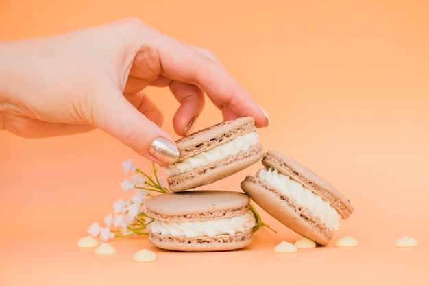 Main de femme avec vernis à ongles doré prenant macaron sur fond coloré