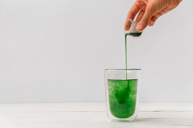 Main de femme versant de la chlorophylle liquide dans une tasse en verre fond blanc avec un espace réservé au texte