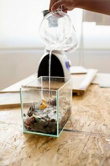 Main de femme versant de l'eau dans un récipient en verre rempli de morceaux de papier