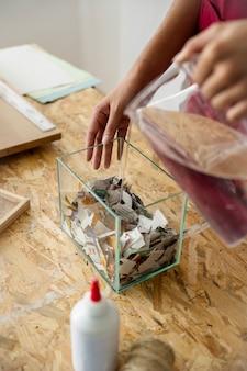 Main de femme versant de l'eau sur des morceaux de papier dans un récipient