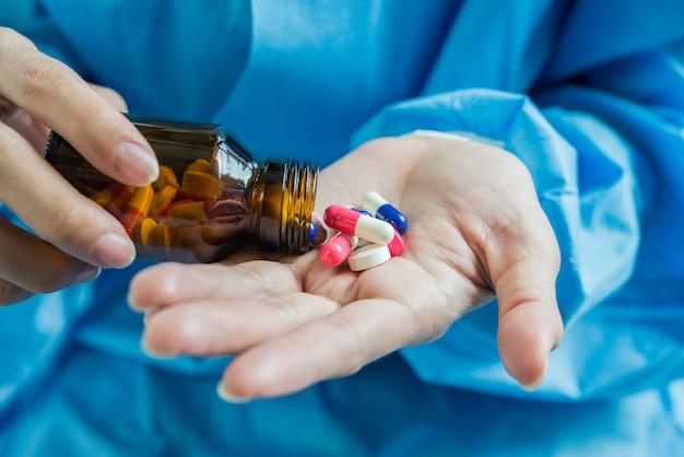 Une main de femme verse les pilules de la bouteille