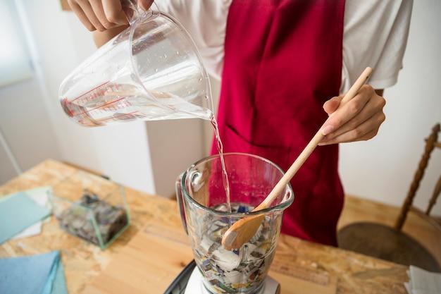 Main de femme verser de l'eau dans un mélangeur rempli de papiers déchirés