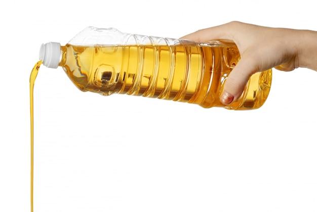 Main de femme, verser l'huile de cuisson de bouteille en plastique. isolé sur blanc.