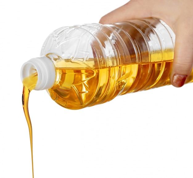Main de femme, verser l'huile de cuisson de bouteille en plastique. isolé sur blanc