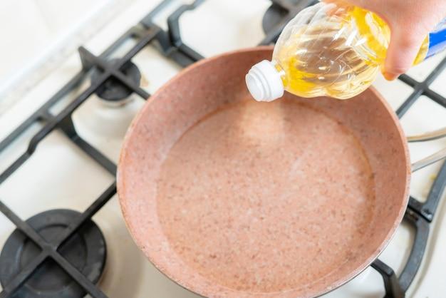 Une main de femme verser de l'huile de cuisson sur la poêle à la maison