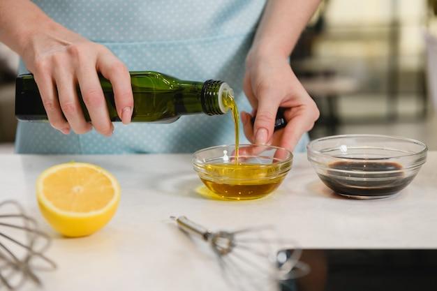 Main de femme verser de l'huile végétale dans un bol