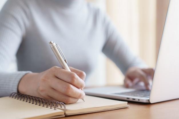 Main de femmes d'affaires à l'aide d'un ordinateur portable et d'un cahier d'écriture tout en étant assis sur le bureau au bureau
