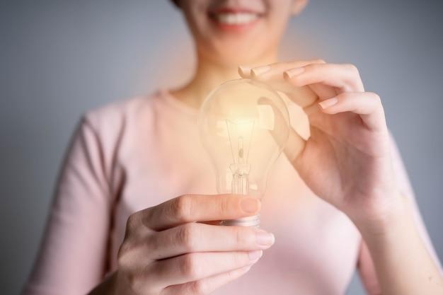 Main de femmes d'affaires tenant une ampoule, concept de nouvelles idées avec innovation et créativité