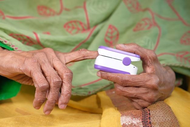 Main de femmes âgées à l'aide de l'oxymètre de pouls.