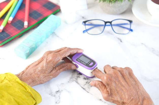 Main de femmes âgées à l'aide d'oxymètre de pouls