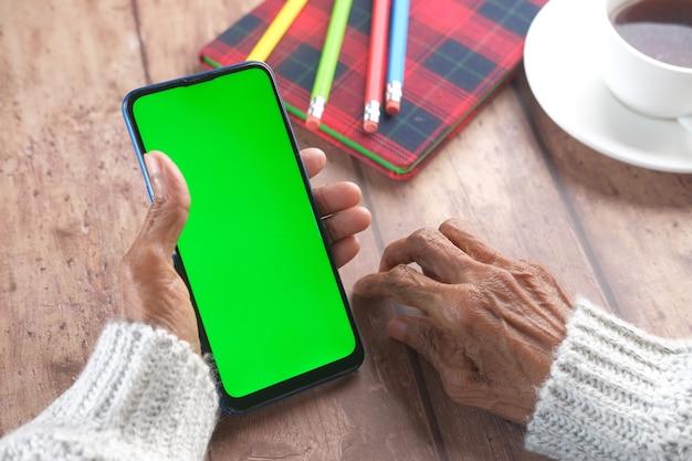 Main de femmes âgées à l'aide de téléphone intelligent se bouchent