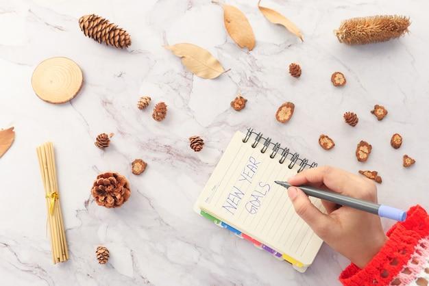 Main de femmes écrivant les objectifs du nouvel an sur papier