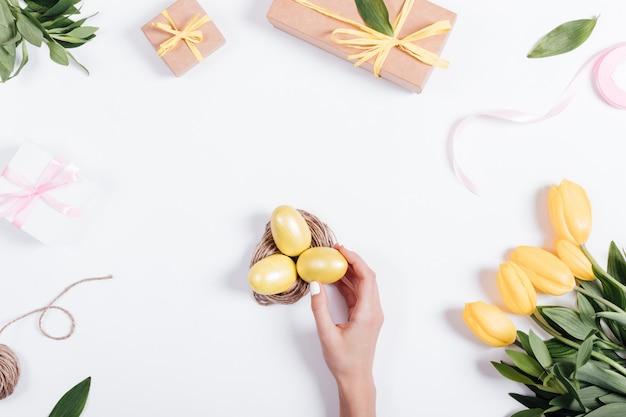 La main des femmes met des oeufs de pâques jaunes dans un nid sur une table près des tulipes