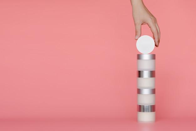 La main des femmes prend le pot du dessus d'une pile de contenants de crème.
