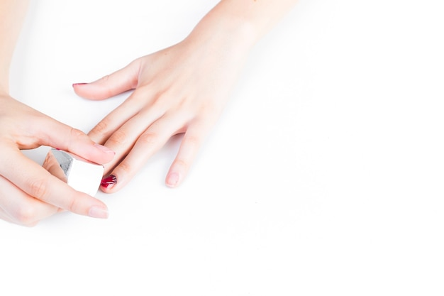 Main de fille, application de vernis à ongles sur fond blanc