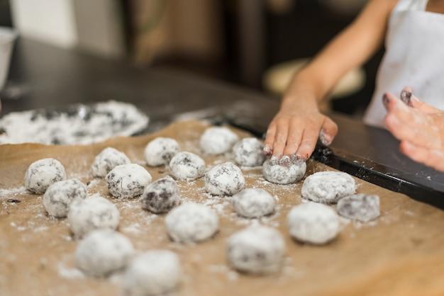 Main de fille appliquant de la farine sur des biscuits crus