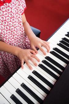 Main de fille closeup jouant du piano