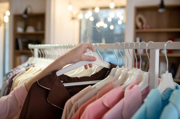 Main d'une fille consultante retirée d'un support avec des vêtements et tenant un trempel avec un costume féminin marron.