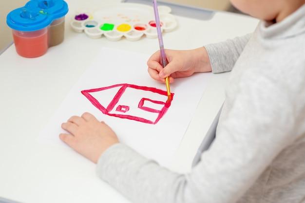 Main d'une fille dessinant une maison rouge.
