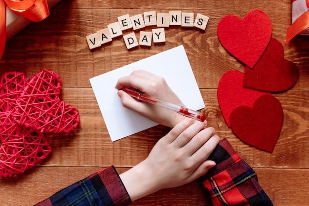 La main de la fille écrit une lettre d'amour. la saint-valentin. carte de voeux à la main avec un coeur rouge en forme de personnage. le 14 février est une célébration de fête. vue d'en-haut