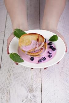 Main de fille gros plan tient une assiette blanche avec des beignets versés par du yogourt avec des tranches de myrtilles et de menthe. une cuillère à café en revanche, un délicieux petit déjeuner et un bon début de journée