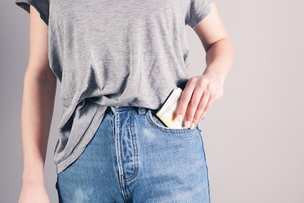 Main de fille mettant de l'argent dans la poche de jeans