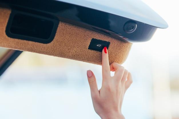 Main de fille ouvrir la section des bagages en voiture