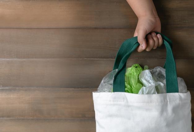 Main fille tenant un sac en toile sur bois