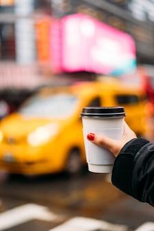 Main d'une fille tenant un verre de café blanc avec un taxi jaune flou en arrière-plan