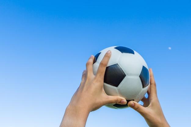 Main de fille tient un ballon de football dans le ciel sur fond de ciel bleu.