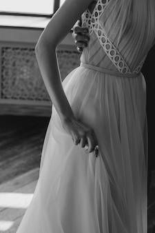 La main des filles soutient l'ourlet d'une robe élégante