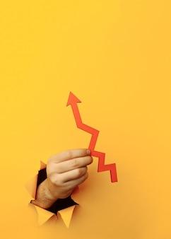 Main avec une flèche rouge vers le haut à travers un trou de papier jaune.