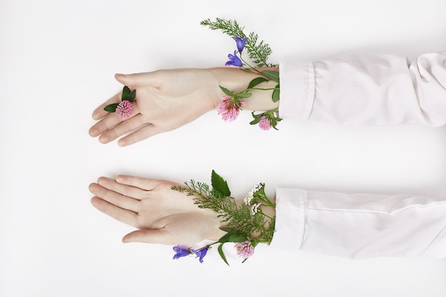 La main et la fleur de couleur printanière se trouvent sur la table.