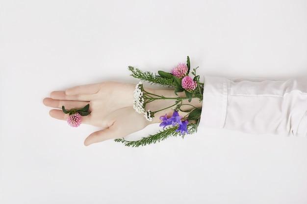 La main et la fleur de couleur printanière sont sur la table