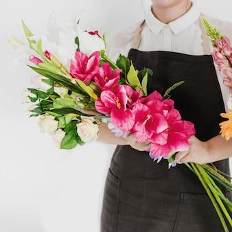 Main de fleuriste femme tenant un bouquet de fleurs blanches et rouges