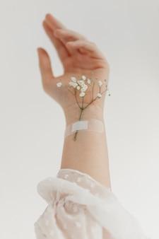 La main avec des fleurs se bouchent